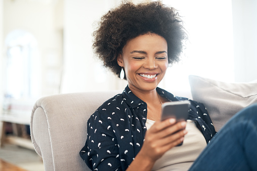 Woman smiling at her cell phone